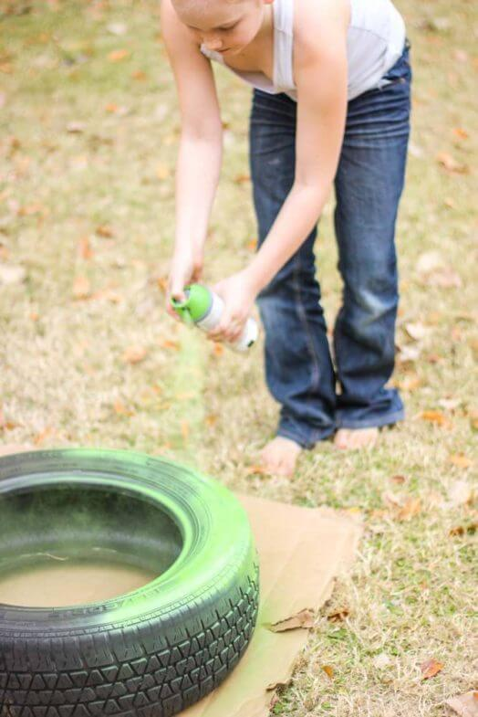 close up of a child spray painting a tire green
