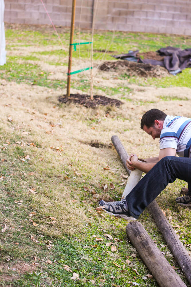 man twisting PVC pipe to dig a hole in a backyard