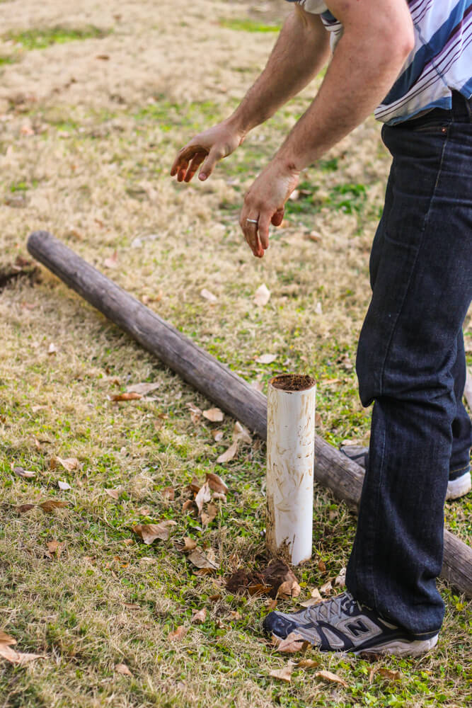 partial shot of man digging a hole with a PVC pipe