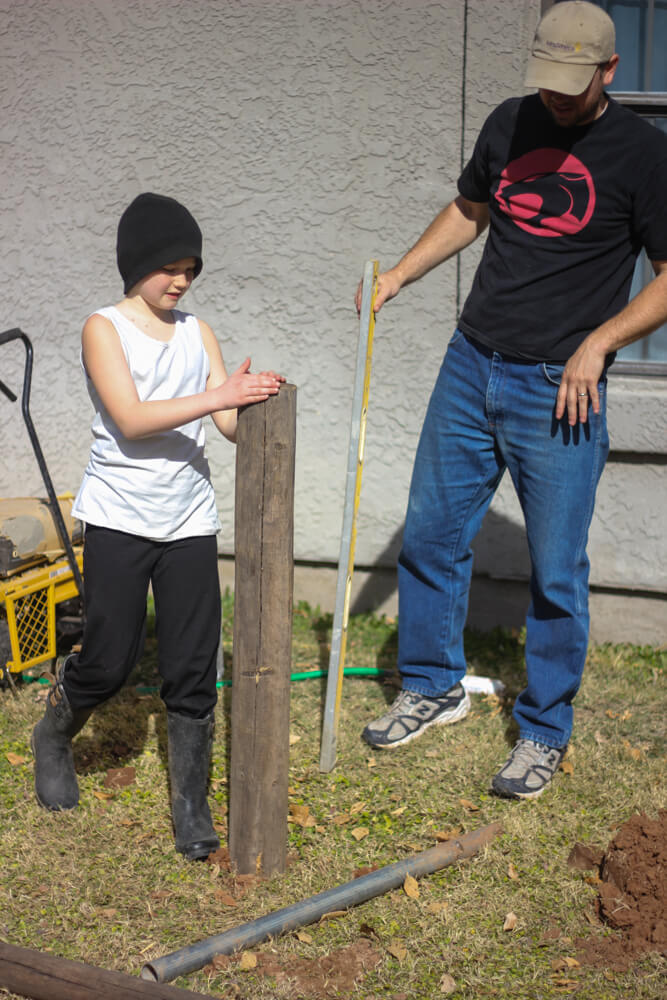 man and child leveling a post inserted in ground