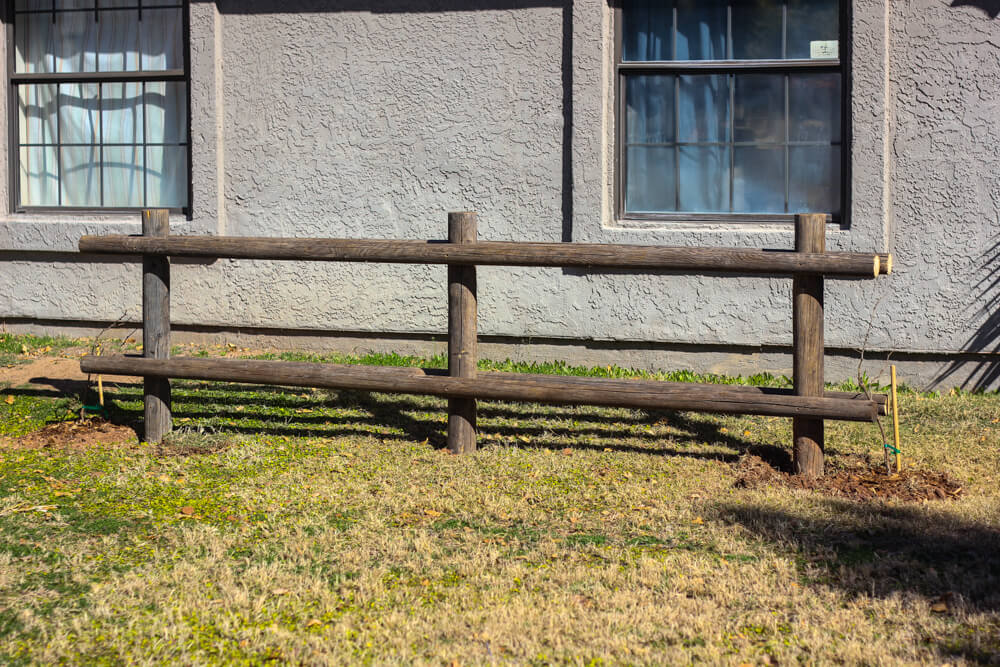wooden pole fence in backyard against house