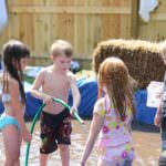 kids playing with a hose in a homemade pool