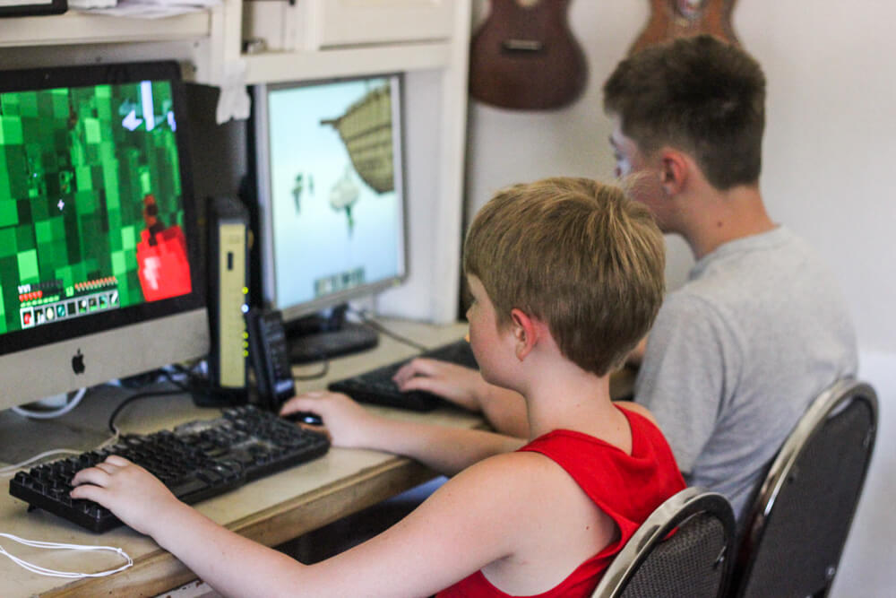 child playing Minecraft on a desktop next to a child playing a computer game on a desktop